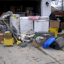 Soaked, wet personal items sitting in a driveway, including a washer and dryer in Mesquite.