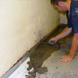 A basement waterproofer installing a perimeter drain system in Flower Mound