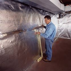 Installation of a radiant heat and vapor barrier on a basement wall in Grapevine